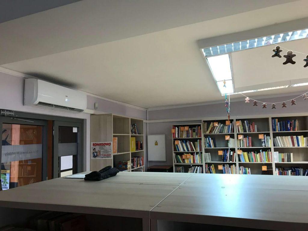 biała klimatyzacja w bibliotece nad drzwiami